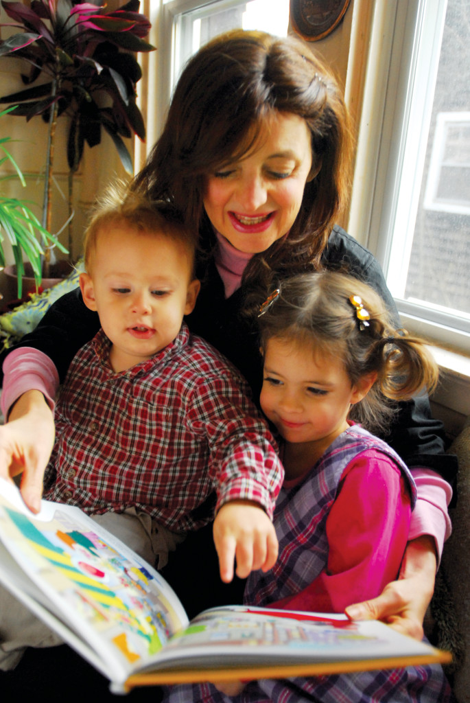 Bracha Goetz reads from one of her recent books to her two grandchildren Chaim Szendro, 1 and a half, and Tzippy, 3 and half.